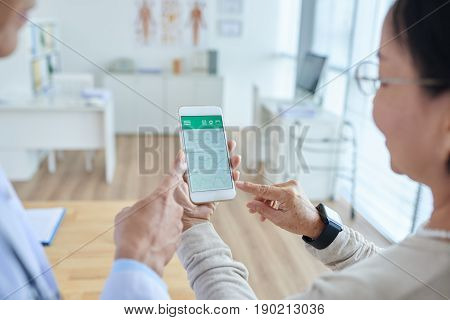 Over shoulder view of middle-aged physician showing his female patient how to use healthcare mobile app, interior of doctors office on background
