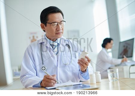 Waist-up portrait of middle-aged Vietnamese doctor sitting at office desk and prescribing pills to patient, blurred background