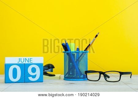 June 9th. Day 9 of month, calendar on yellow background with office suplies. Summer time at work. International Friends Day. Archives DAY.