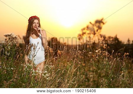 Young, beautiful, attractive model in swimsuit, posing in a field of flowers on the background of sunset, hairstyle, makeup, red crown, portrait.