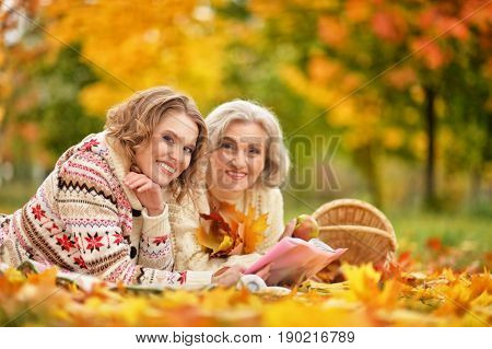 Senior woman with daughter resting in autumnal park