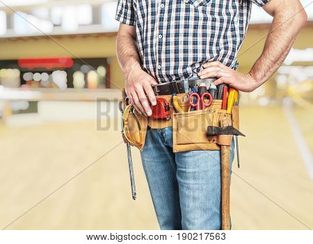 detail of handyman with toolsbelt and blurred background