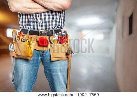 handyman with toolsbelt and crossed arms blurred background