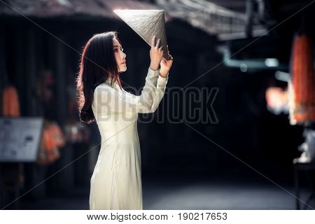 Young Beautiful woman in Ao Dai Vietnam traditional dress holding a hat of portrait vietnamese culture. poster