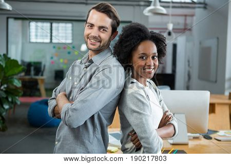 Portrait of happy man and woman standing back to back in creative office