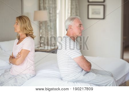 Upset senior couple sitting back to back on bed in bedroom