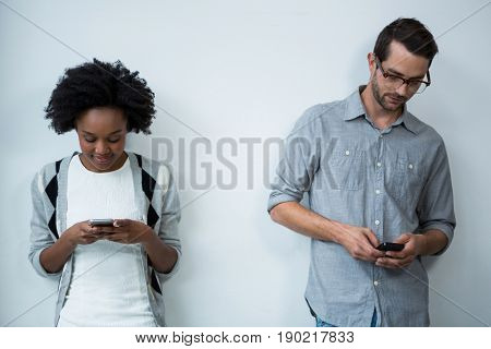 Man and woman standing against white wall and using mobile phone in office