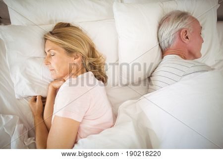 Senior couple sleeping back to back on bed in bed room