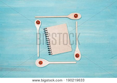 Top View Of Wooden Spoons With Cherry Tomatoes And Closed Cookbook With Blank Cover On Wooden Table