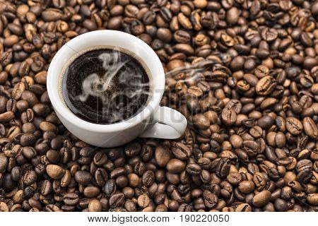 cup of steaming coffee on bunch of roasted coffee beans