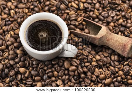 cup of coffee on roasted coffee beans with wooden scoop.