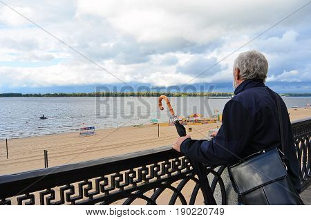 Old man holding vintage umbrella looking far on the river beach outdoors sky background. Back side view of traveller explorer. Tourist senior