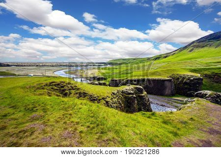 Green Icelandic Tundra in July. Magic canyon Fyadrarglyufur. Fast river with glacial water flows among cliffs. The concept of active northern tourism