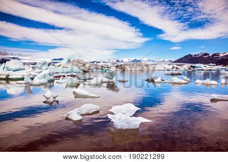 Cirrocumulus magically reflected in the smooth water of the lagoon. The concept of northern extreme tourism. The ice floes and cirrocumulus clouds of lagoon Jokulsarlon, Iceland