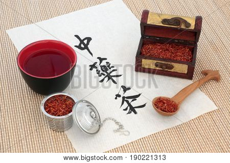 Chinese safflower herb tea with calligraphy on rice paper, tea cup, old wooden caddy box and spoon, also used in alternative herbal medicine. Translation reads as chinese herb tea.