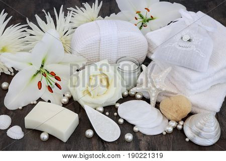 Rose and white lily flower cleansing skincare beauty treatment including moisturizing cream, soap, flannels, salt, natural sponge with shells and pearls.