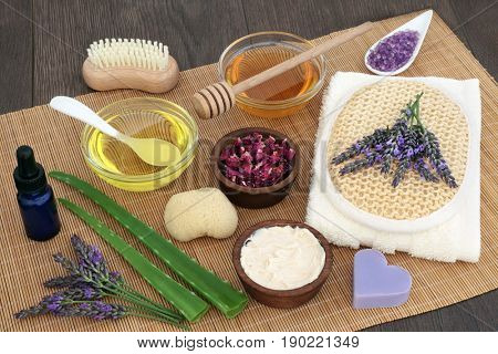 Herbal skincare ingredients to soothe skin disorders with lavender flowers, aloe vera and rose petals on bamboo over oak wood background.