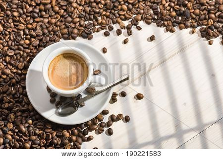 cup of coffee with coffee beans on wooden table illuminated by sunlight coming through the window.