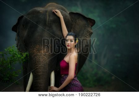 Thai beautiful women in traditional dress and elephant in wild with concept fashion people and elephant To lovers of elephants in Thailand and in the world.