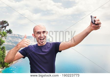 Young man taking travel selfie on trekking excursion day - Hipster guy self photo at view point with blue ocean background - Concept of healthy lifestyle in beauty of nature.