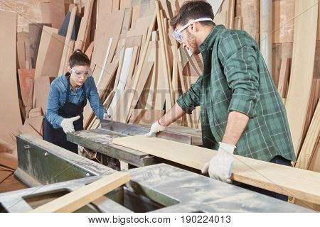 Carpenters with googles cutting wood in cooperation