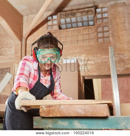 Woman cutting wood with grinder during her apprenticeship