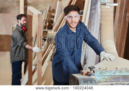 Man as carpenter with jack plane during carpentry workshop