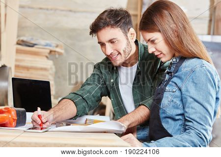 Man teaching woman during carpenter apprenticeship
