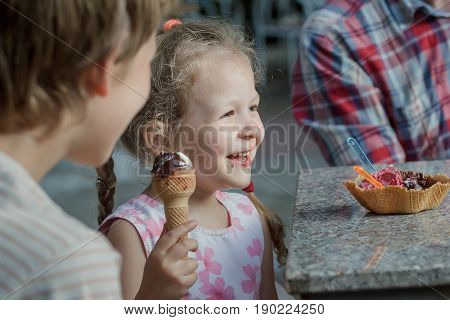 Little girl and her brother are laughing during eating Italian ice cream