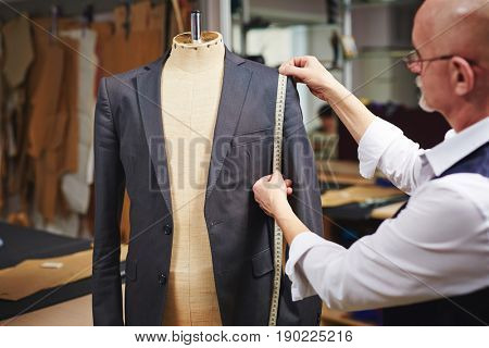 Portrait of mature tailor measuring jacket with tape fitting custom suit on mannequin