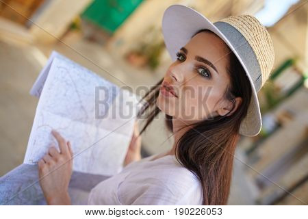 Tourist woman with a map in a small Italian town