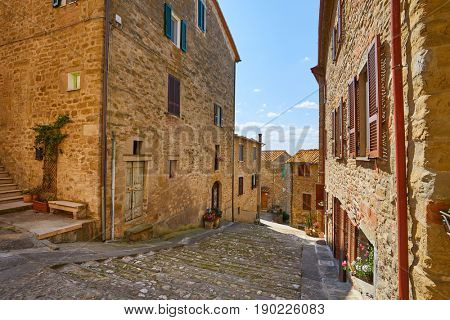 Beautiful narrow alley with traditional historic houses at old city in Tuscany