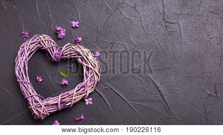 Decorative heart and little lilac flowers on black textured background. Top view. Place for text.
