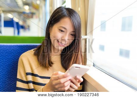 Woman sending sms on mobile phone in train