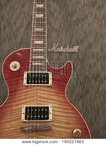 The classic rock combination of a Gibson Les Paul electric guitar leaning against a Marshall amplifier in a music retail shop