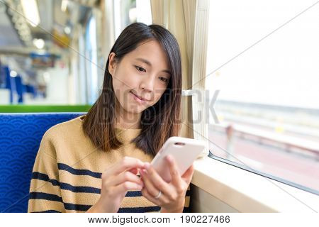 Woman sending sms on cellphone inside a train