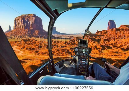 Helicopter cockpit with pilot arm and control console inside the cabin on scenic flight of Monument Valley Navajo Tribal Park, Arizona and Utah, America.
