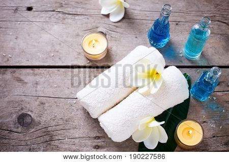 Spa or wellness setting. Towels bottles with oil and white plumeria flower on wooden background. Selective focus. Place for text.