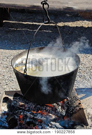 Cooking large pot over the fire outdoors in camp