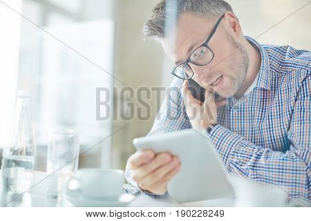 Busy middle-aged manager in eyeglasses dictating information to colleague on the phone while he using tablet