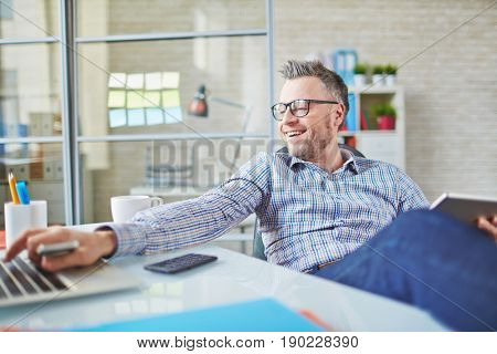 Optimistic middle-aged businessman enjoying easy work with modern devices, he typing on laptop and sitting at desk in office