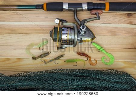 Silicone spoon-baits with a sachet and a spinning coil оn a wooden table