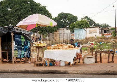 Ivorian African woman with her daughter selling bread in the street market. Yamoussoukro, Ivory Coast, July 2013.