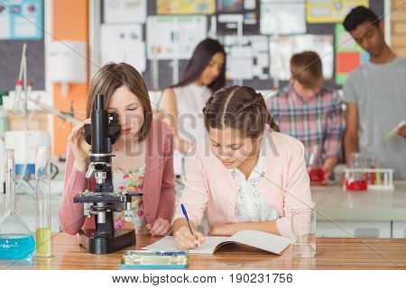 Students experimenting on microscope in laboratory at school in laboratory at school