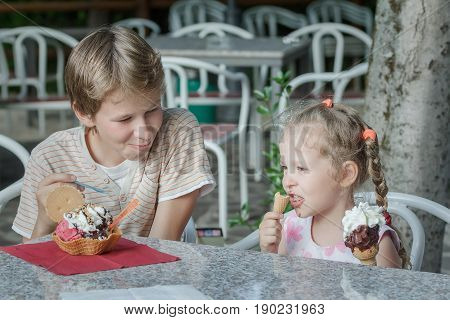 Portrait of two siblings are eating Italian gelato ice cream in cafe