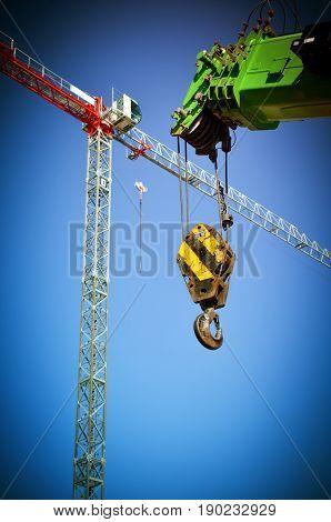 High construction cranes against the blue sky