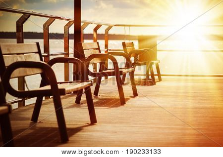 Amazing beach landscape with chairs for relaxation on wooden terrace. Bright sun rays. Travel background in vintage style.