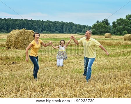 Parents having fun with little daughter on mowed field of wheat with hays