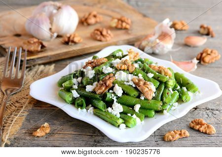 Delicious warm green beans salad with balsamic dressing. Green bean salad with cottage cheese, walnuts, garlic and spices on a plate and a vintage wooden table. Side dish or vegetarian main dish
