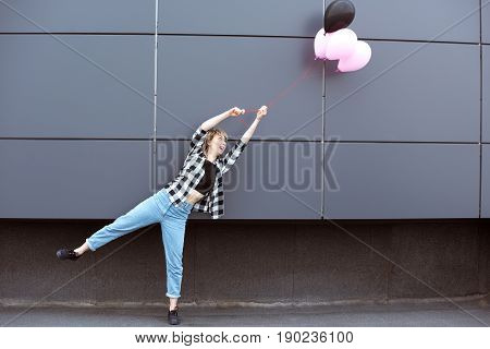 Young Casual Girl Fooling Around With Air Balloons Outdoors